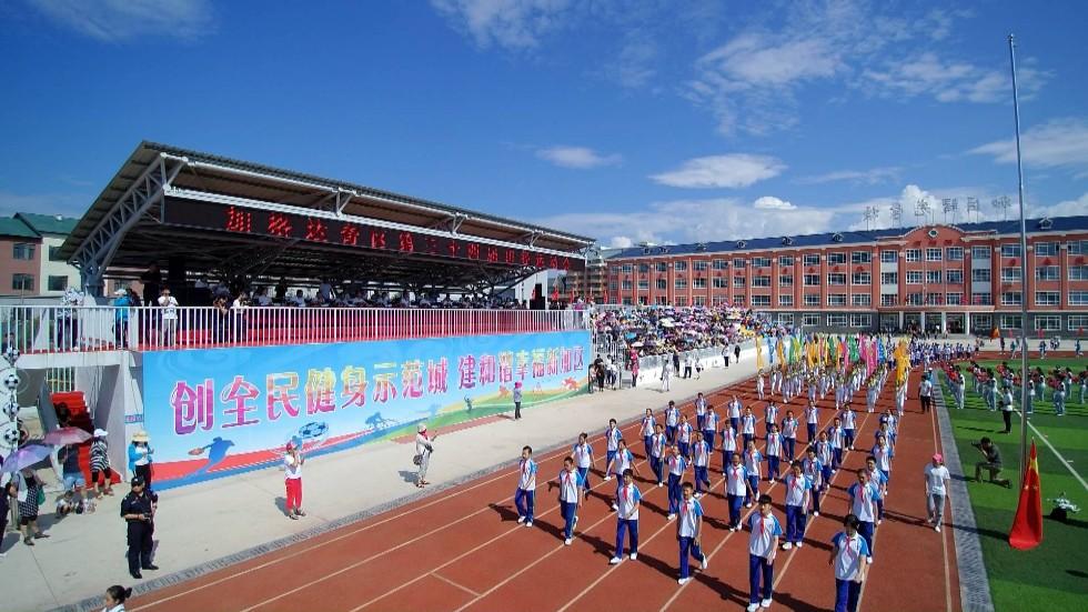 护拥着鲜艳的五星红旗和第三十四届田径运动会会旗走进体育场.